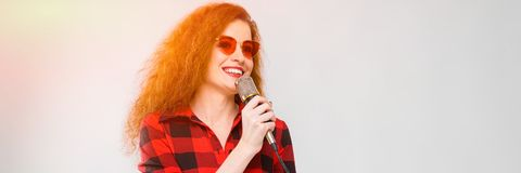 Portrait of beautiful redhead happy young woman in sunglasses smiling holding microphone on gray background stock image