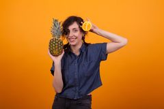 Attractive caucasian young woman holding a pineapple in her hand over a yellow background in studio. Woman with delicious exotic fruits royalty free stock images