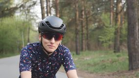 Attractive causcasian girl starts riding bicycle. Focused woman on bicycle. Girl wearing helmet and glasses on a bike. stock video