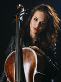 Attractive cello player and her instrument. Photo of a beautiful woman posing with her old cello Royalty Free Stock Images