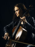 Attractive cello player playing her instrument. Photo of a beautiful woman playing her old cello Stock Images
