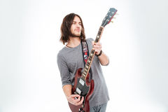 Attractive charismatic male guitarist standing and playing electric guitar Royalty Free Stock Photos