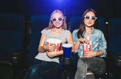 Attractive and charming girls are sitting in chairs in cinema. Each of them has a different size of baskets with popcorn. Brunette is eating popcorn while Stock Photos