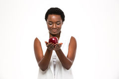 Attractive cheerful african woman holding big red apple on palms Stock Photography