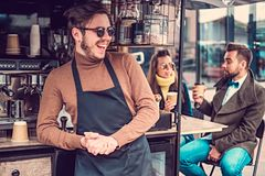 Attractive cheerful barista in sunglasses took a coffeebreak at his own coffeeshop.  royalty free stock images