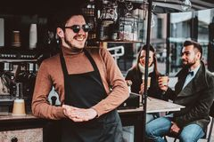 Attractive cheerful barista in sunglasses took a coffeebreak at his own coffeeshop.  stock photos