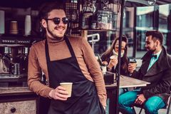 Attractive cheerful barista in sunglasses took a coffeebreak at his own coffeeshop.  stock image