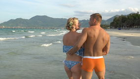 Attractive cheerful couple walking at beach. Hug each other and kiss