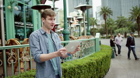 Attractive cheerful guy is doing a video translation while standing on a street by using his tablet pc. Young handsome is standing on a sidewalk and having a stock footage
