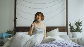 Attractive cheerful woman dancing and singing with comb like microphone sitting in bed at home royalty free stock image