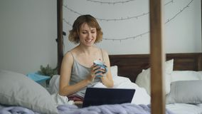 Attractive cheerful woman having online video chat with friends using laptop camera while sitting on bed at home stock photography