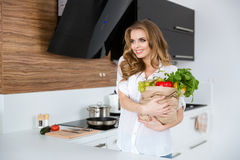 Attractive cheerful woman holding packet full of healthy food Stock Photos