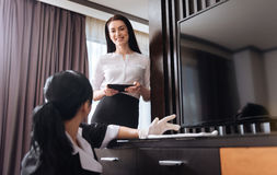 Attractive cheerful woman looking at the hotel maid Stock Photo