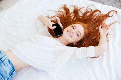Attractive cheerful woman lying and holding mobile phone Stock Photos