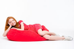 Attractive cheerful woman lying on red bean bag Royalty Free Stock Photography