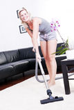 Attractive cheerful woman is in the room with vacuum-cleaner. Stock Image