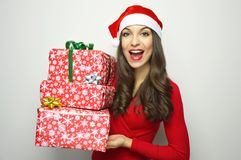 Attractive cheerful woman with Santa Claus hat holding her presents on gray background Royalty Free Stock Photo