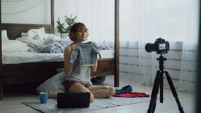 Attractive cheerful woman sitting near bed recording video blog about children`s clothes with dslr camera at home Stock Image