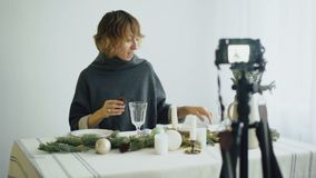 Attractive cheerful woman sitting at the table recording video blog about food decoration design on camera. At home stock video footage