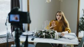 Attractive cheerful woman sitting at the table recording video blog about food decoration design on camera. At home stock video
