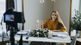 Attractive cheerful woman sitting at the table recording video blog about food decoration design on camera. At home royalty free stock photos
