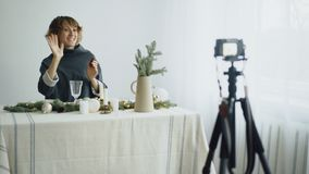 Attractive cheerful woman sitting at the table recording video blog about table setting design on camera stock images