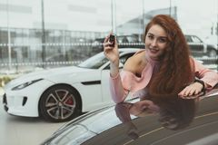 Happy woman holding car keys to her new automobile stock images