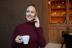 Attractive cheerful woman speaking on mobile phone with friend while enjoying cup of cappuccino in modern cafe, Royalty Free Stock Photos