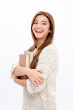Attractive cheerful woman in white clothes standing and holding books Royalty Free Stock Images