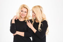 Attractive cheerful young blonde sisters twins talking and looking away Stock Image