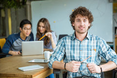 Attractive cheerful young curly malestudying with students in classroom Royalty Free Stock Photo