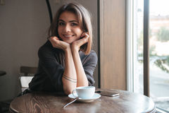 Attractive cheerful young lady in cafe drinking coffee. Royalty Free Stock Photography