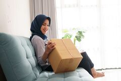 The attractive and cheerful young muslim business woman is working on the package and smiling while sitting at her