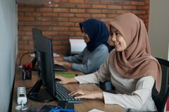 Attractive cheerful young muslim business woman working on computer and smiling while sitting at her desk modern office