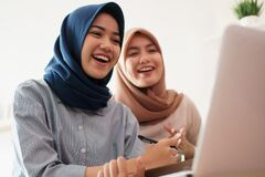 Attractive cheerful young muslim business woman working on laptop and smiling while sitting at her desk modern office