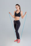 Attractive cheerful young sportswoman exercising with jumping rope Royalty Free Stock Photos