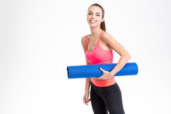 Attractive cheerful young sportswoman holding yoga mat Royalty Free Stock Photography