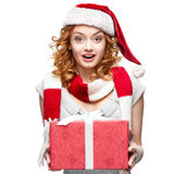 Attractive cheerful young woman in santa hat holding gift Stock Photography