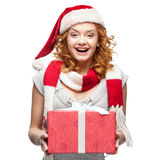 Attractive cheerful young woman in santa hat holding gift Royalty Free Stock Photo