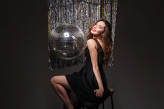 Attractive cheerful young woman sitting near disco ball Stock Image