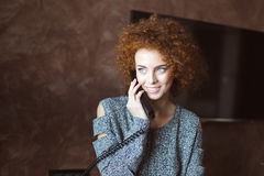 Attractive cheerful young woman talking on telephone at home Stock Photos