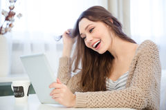 Attractive cheerful young woman using tablet  and laughing at home Royalty Free Stock Images