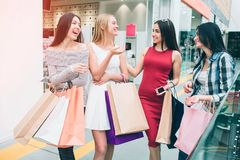 Attractive and cheerful young women are talking with each other and smiling. They have many shopping bag in hands. Girl. In red dress holds phone Royalty Free Stock Photos