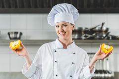 Attractive chef showing halves of bell pepper. At restaurant kitchen royalty free stock photo