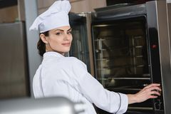 attractive chef standing near oven royalty free stock photos
