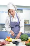 Attractive chief cook preparing food. Cuts broccoli royalty free stock photos