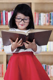 Attractive child with book in library Stock Image