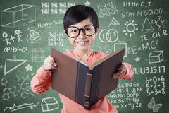 Attractive child with book and scribble background Royalty Free Stock Photos