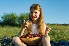 Attractive child girl eating strawberry. Nature background, green meadow, country style.  royalty free stock image