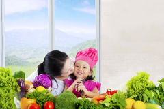 Attractive child with mom and vegetables Royalty Free Stock Photos